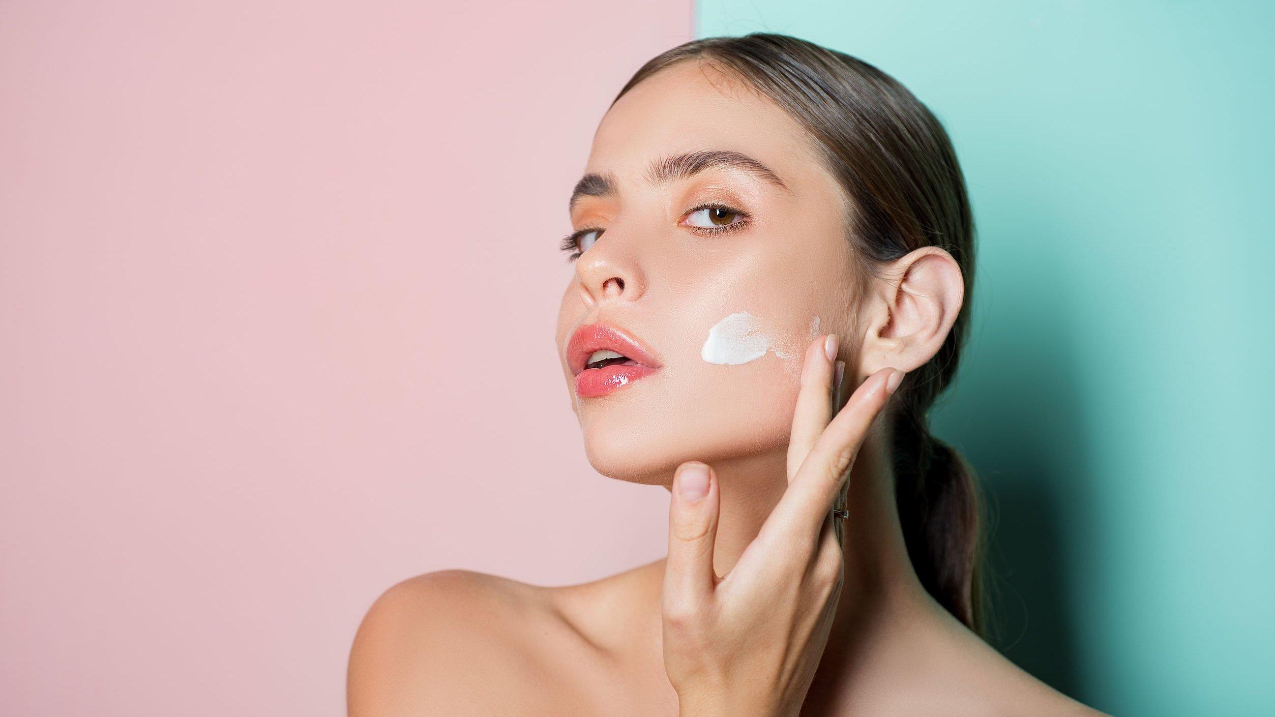 Retrato de uma linda jovem tocando a bochecha com a mão, aplicando creme facial.