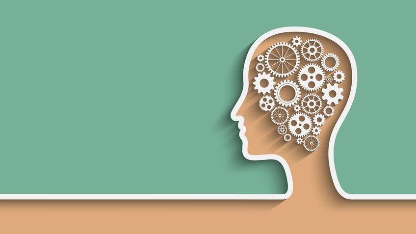 Desenho de uma cabeça humana sob fundo verde, na qual há engrenagens onde seria o cérebro