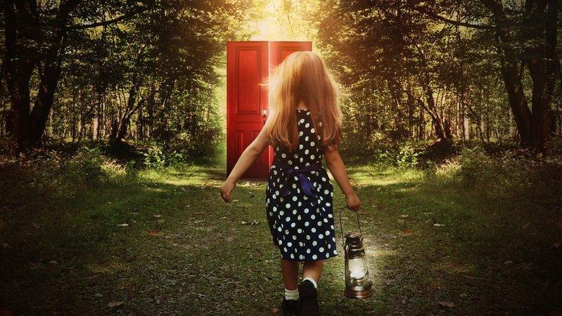 Menina caminhando em floresta em direção a porta vermelha