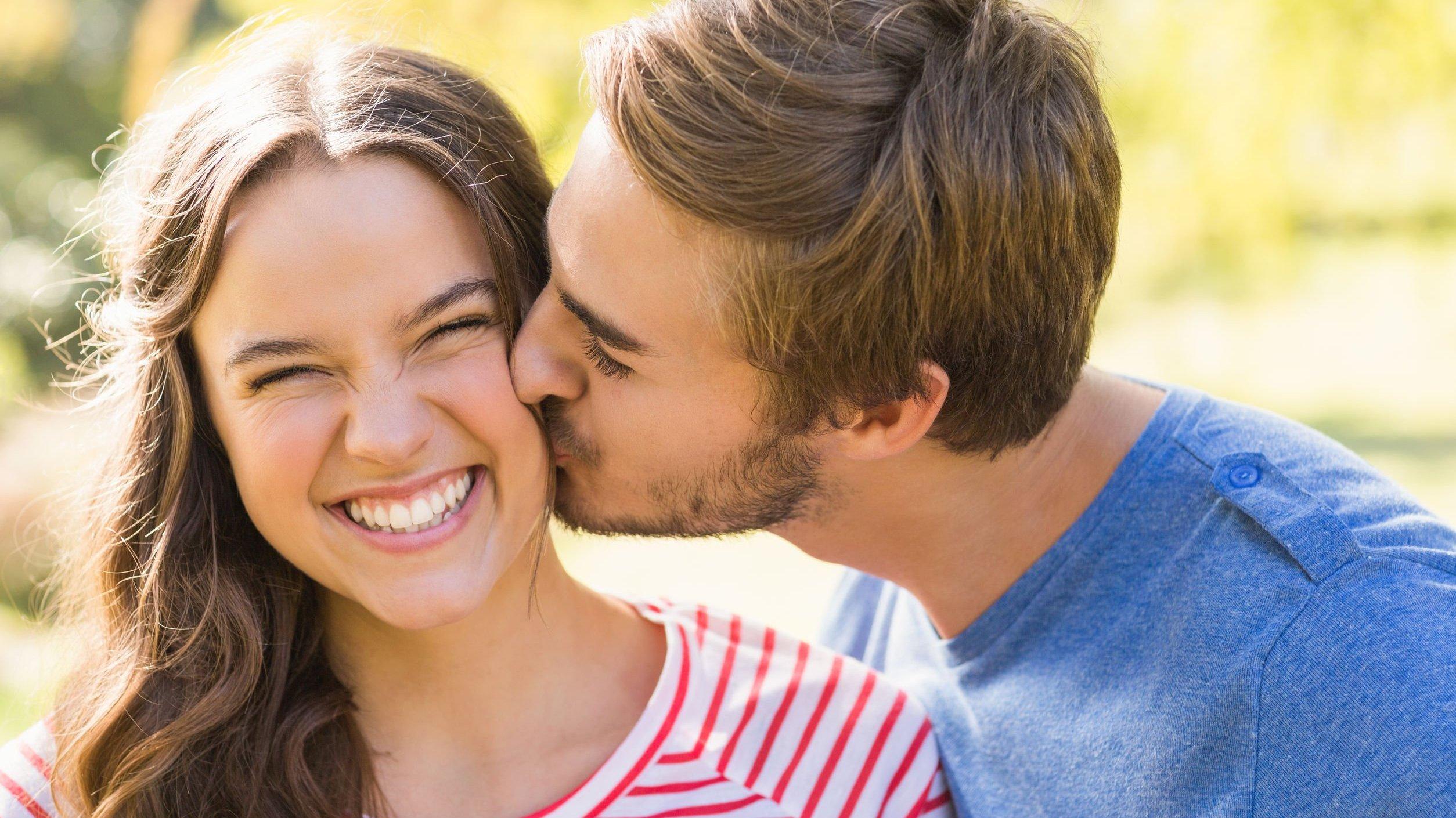 Homem beija bochecha de mulher.