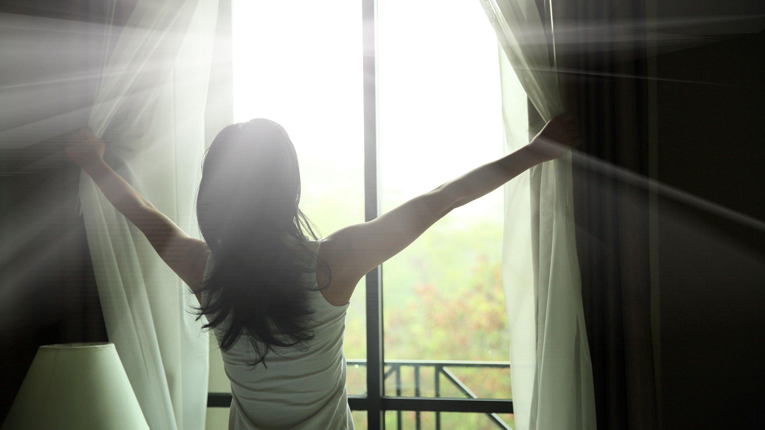 Mulher abrindo cortina