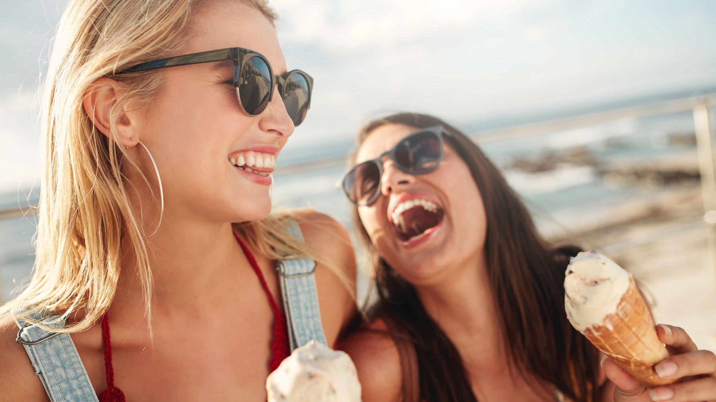 Duas amigas rindo e tomando sorvete