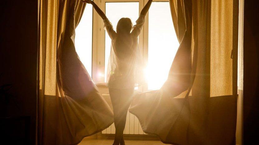 Mulher abrindo a janela em com sol refletindo
