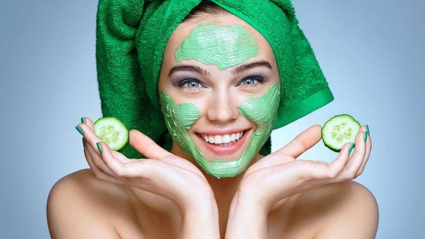 Mulher aplicando máscara skin care verde