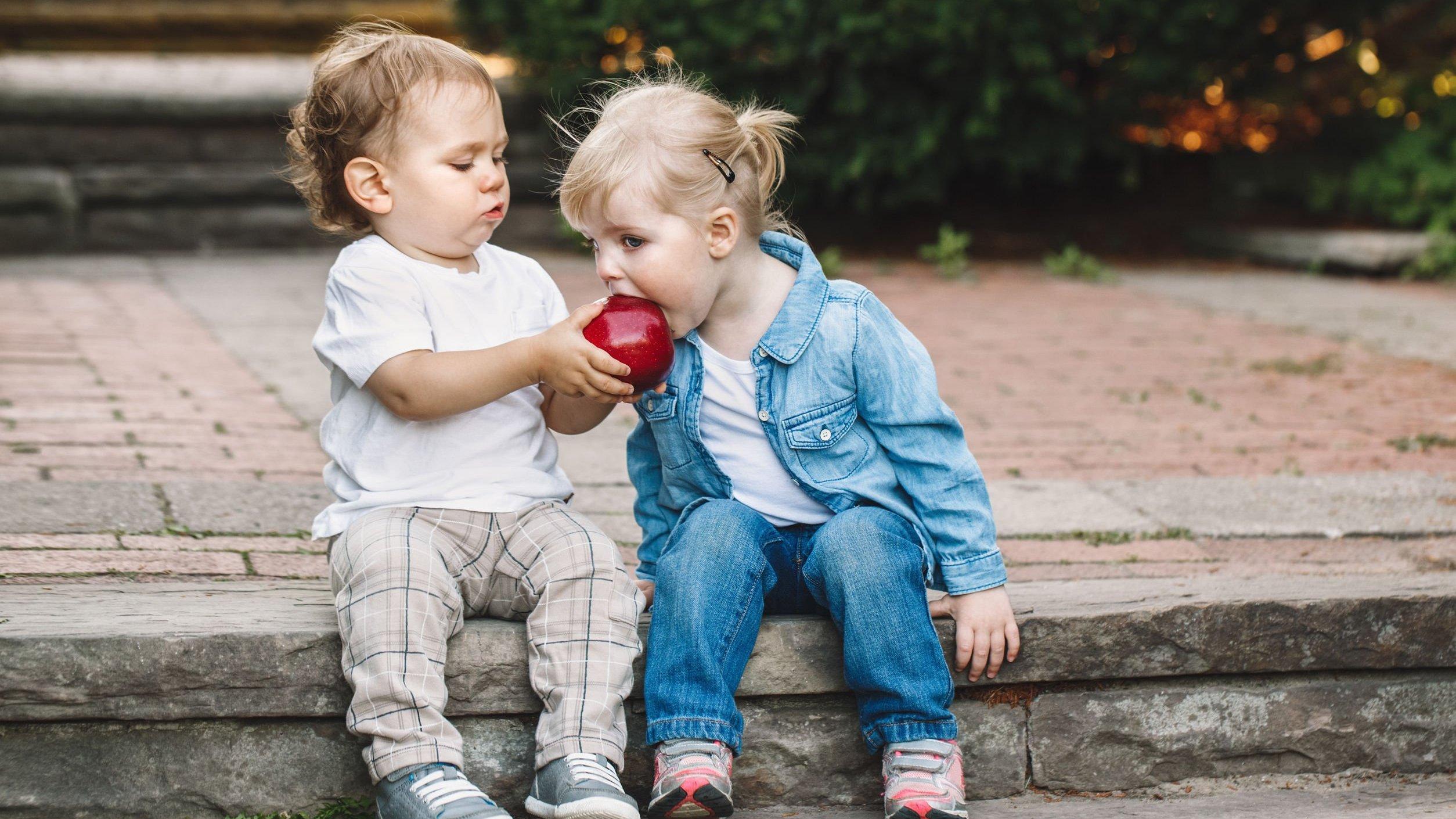 Menino e menina pequenos, sentados em uma sarjeta. O menino segura uma maçã, e a menina dá uma mordida nela.