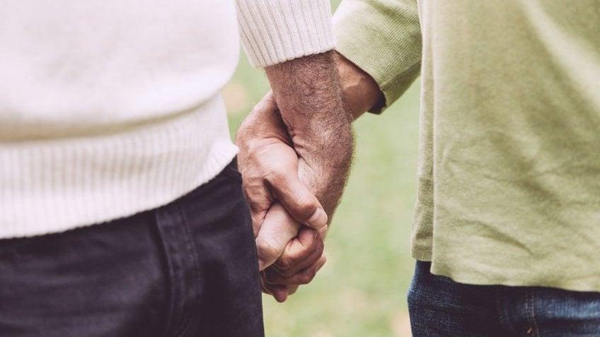 Mãos de casal juntas.