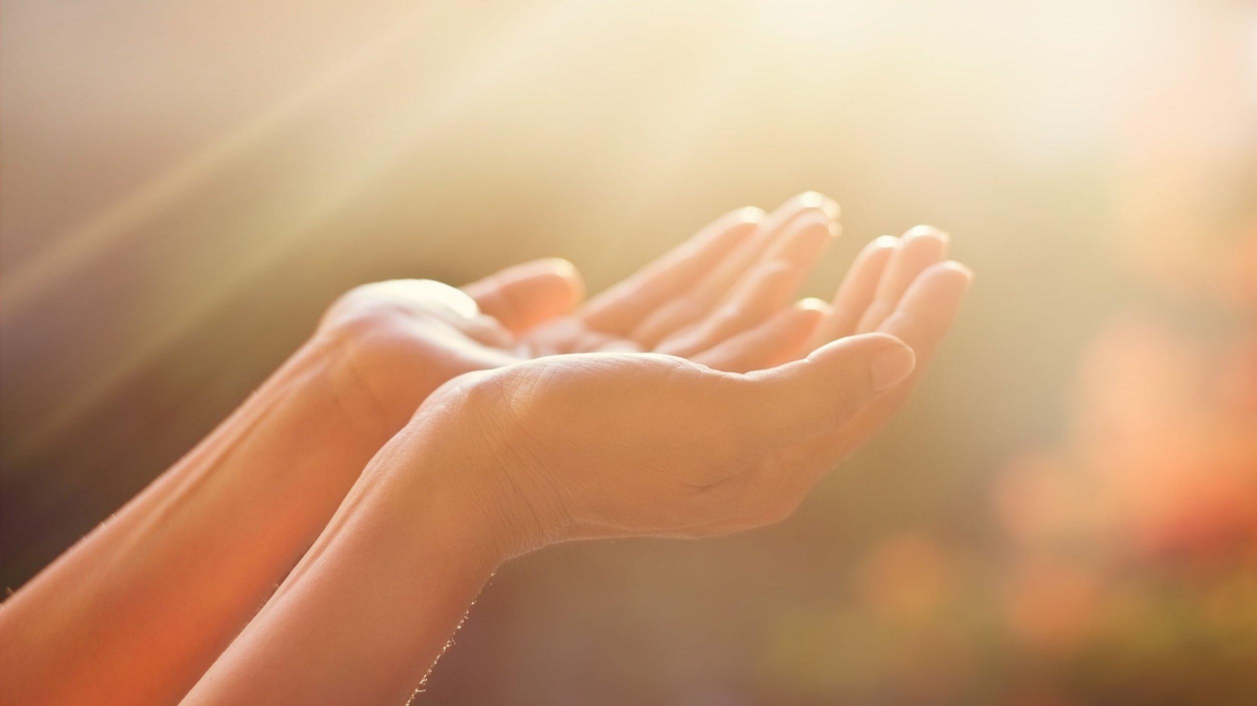 Mãos com as palmas voltadas para cima, sob a luz do sol.
