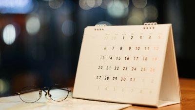 Calendário em uma mesa junto com um óculos redondo