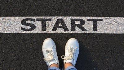 Mulher de braços abertos sorrindo na praia