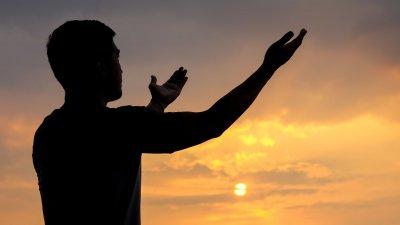 Silhueta de um homem com braços abertos ao pôr do sol