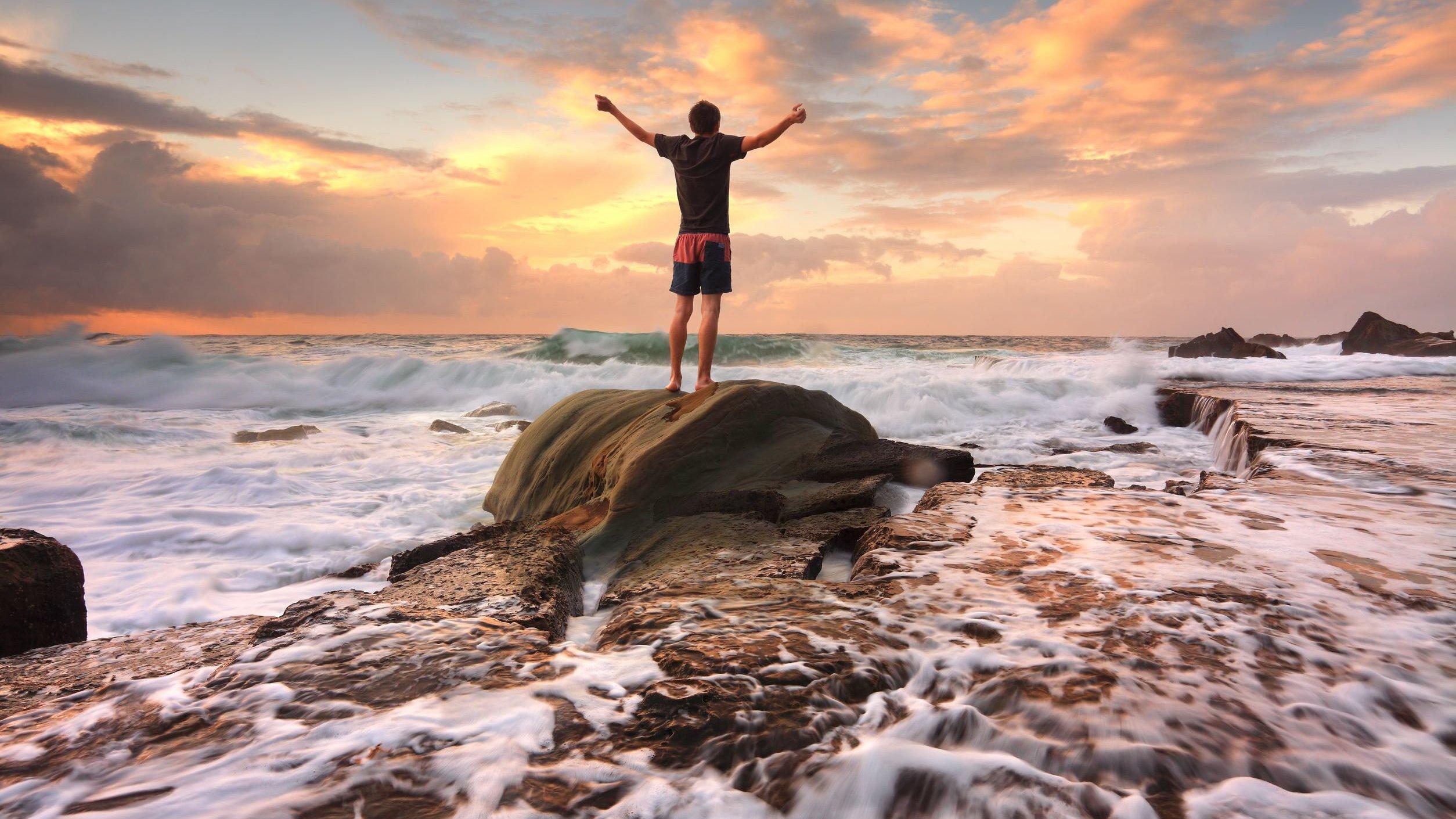 Homem de pé em uma pedra, na praia, de braços abertos.