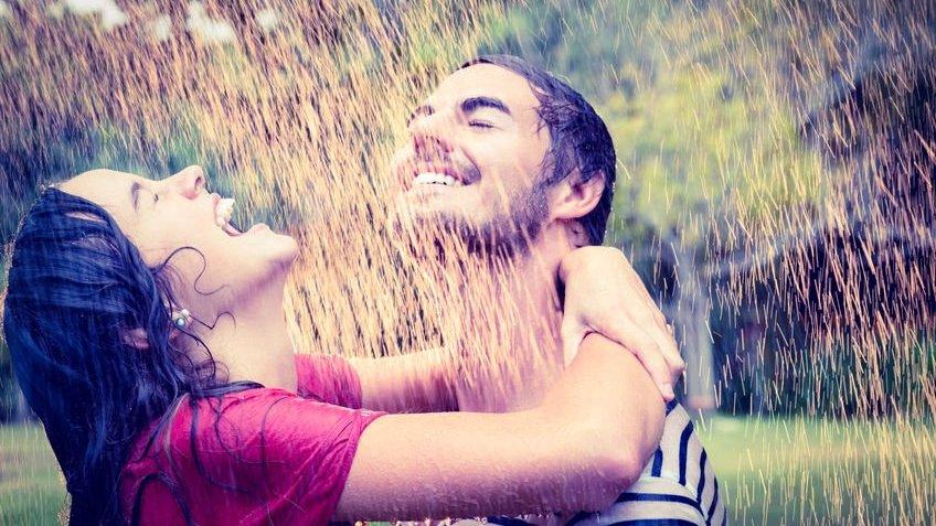 Casal abraçado sorrindo tomando chuva