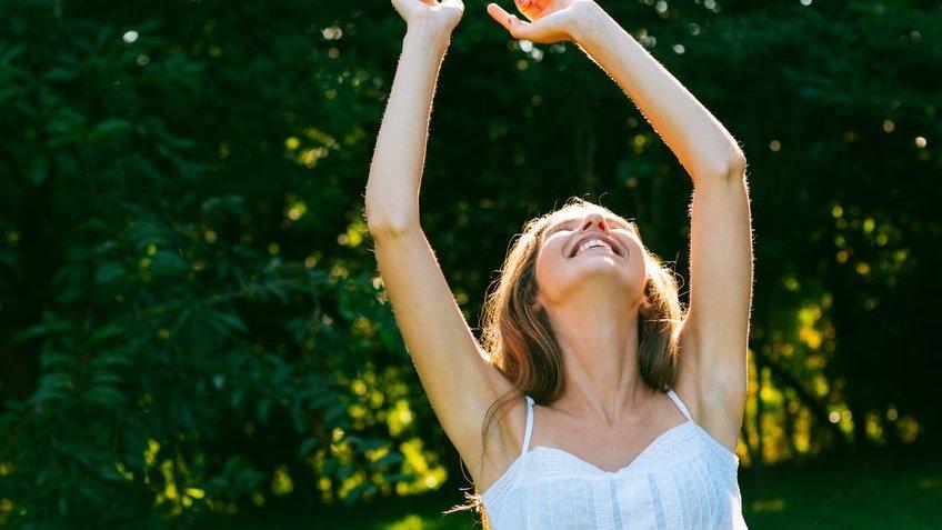Mulher com braços para cima sorrindo com fundo de folhar verdes sob o sol