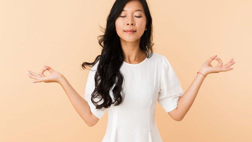 Mulher meditando de olhos fechados.