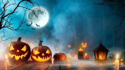 Abóboras e lamparinas acesas num deck de madeira durante a noite.
