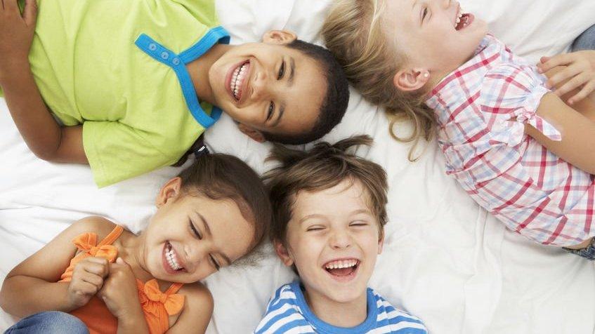 Crianças deitadas na cama, rindo