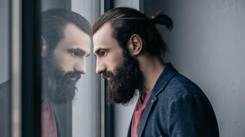homem olhando para o reflexo no vidro