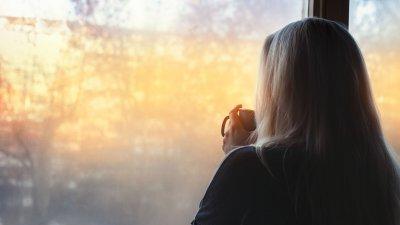Mulher de costas para a câmera, olhando para uma janela que mostra árvores e a luz amarela do sol, enquanto segura uma caneca.