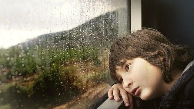 Menino olhando chuva pela janela