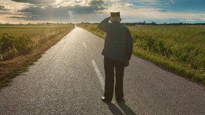 Senhor de costas em estrada olhando o sol refletindo ao fundo
