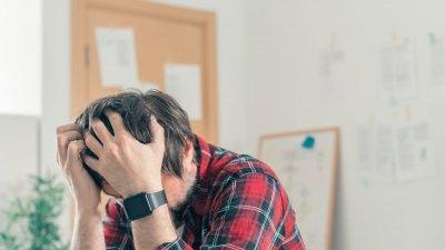 Homem com expressão cansada e olhos fechados, com uma de suas mãos em seu rosto.