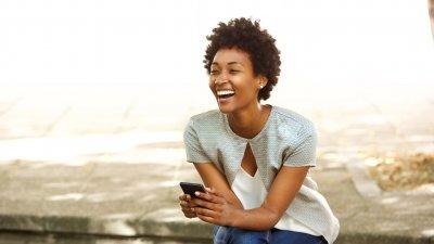 Mulher sorrindo enquanto segura um celular