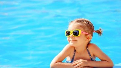 Criança apoiada na beira da piscina sorrindo