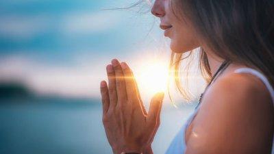 Mulher vista de perfil com as mãos unidas, ao pôr do sol