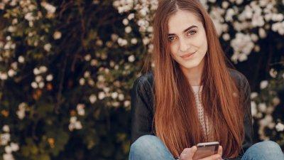 Mulher segurando o celular e sorrindo