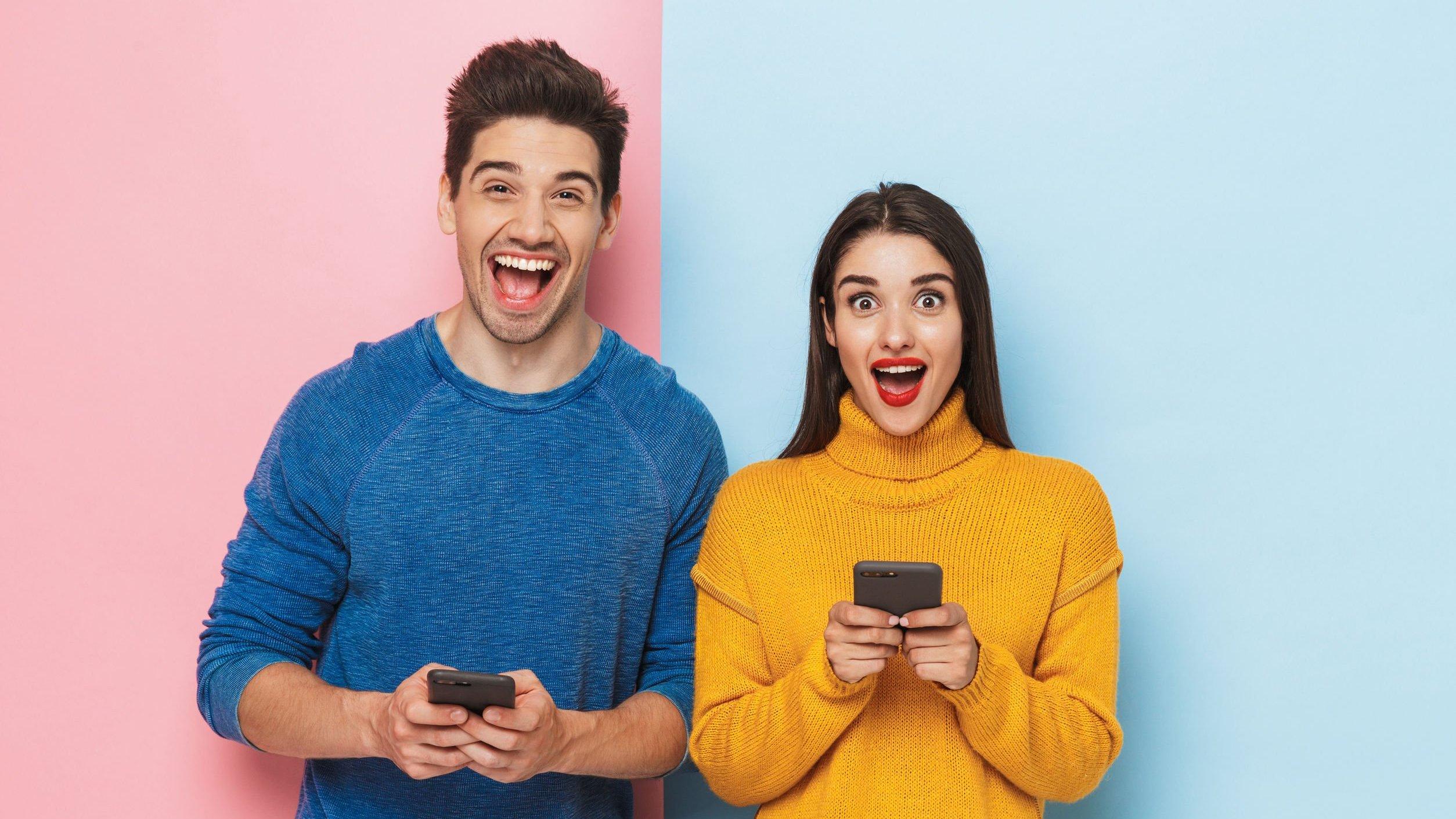 Homem e mulher segurando smartphones enquanto sorriem, lado a lado.
