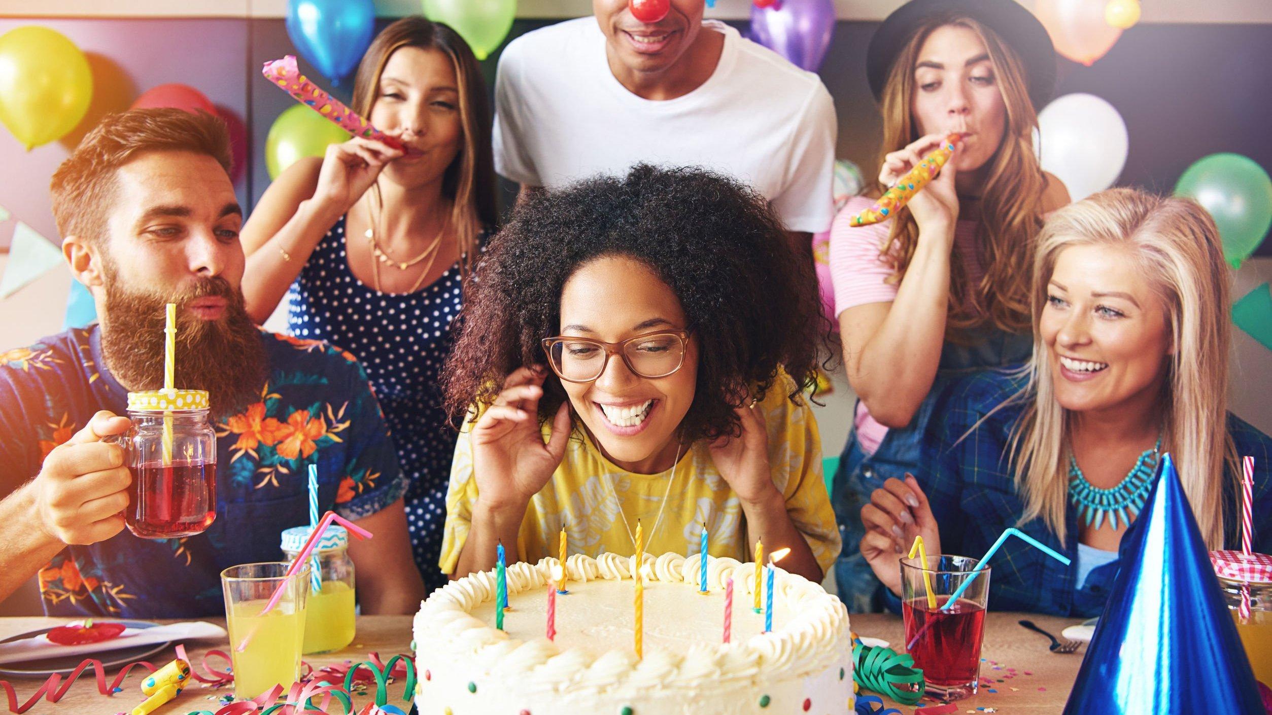 Mulher sorrindo com bolo em sua frente, enquanto pessoas a sua volta assopram línguas-de-sogra.