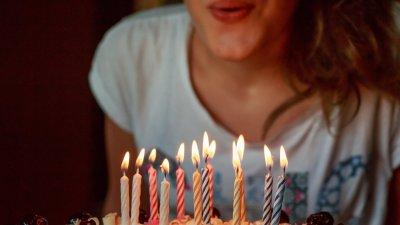 Mulher assoprando velas de bolo de aniversário