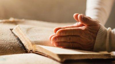 Mãos apoiadas em bíblia