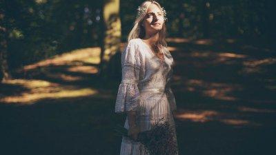 Mulher branca e loira numa floresta, com luz do sol no rosto.