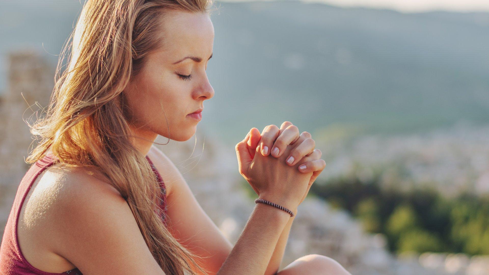 Mulher loira rezando no topo de uma montanha
