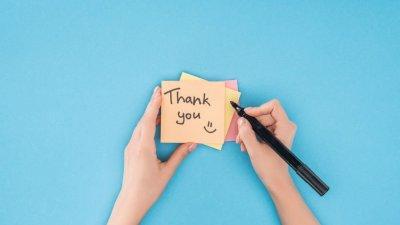 Pessoa com caneta preta escrevendo Thank You em post-it
