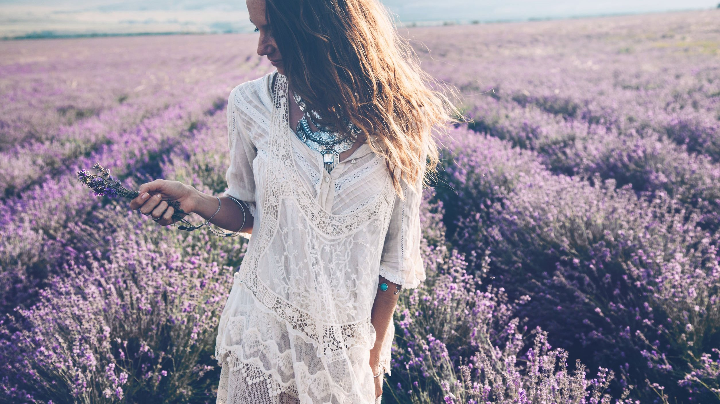 Mulher branca e loira, vestindo vestido branco, num campo de lavanda.