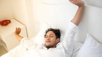 Homem se espreguiçando em sua cama durante a manhã