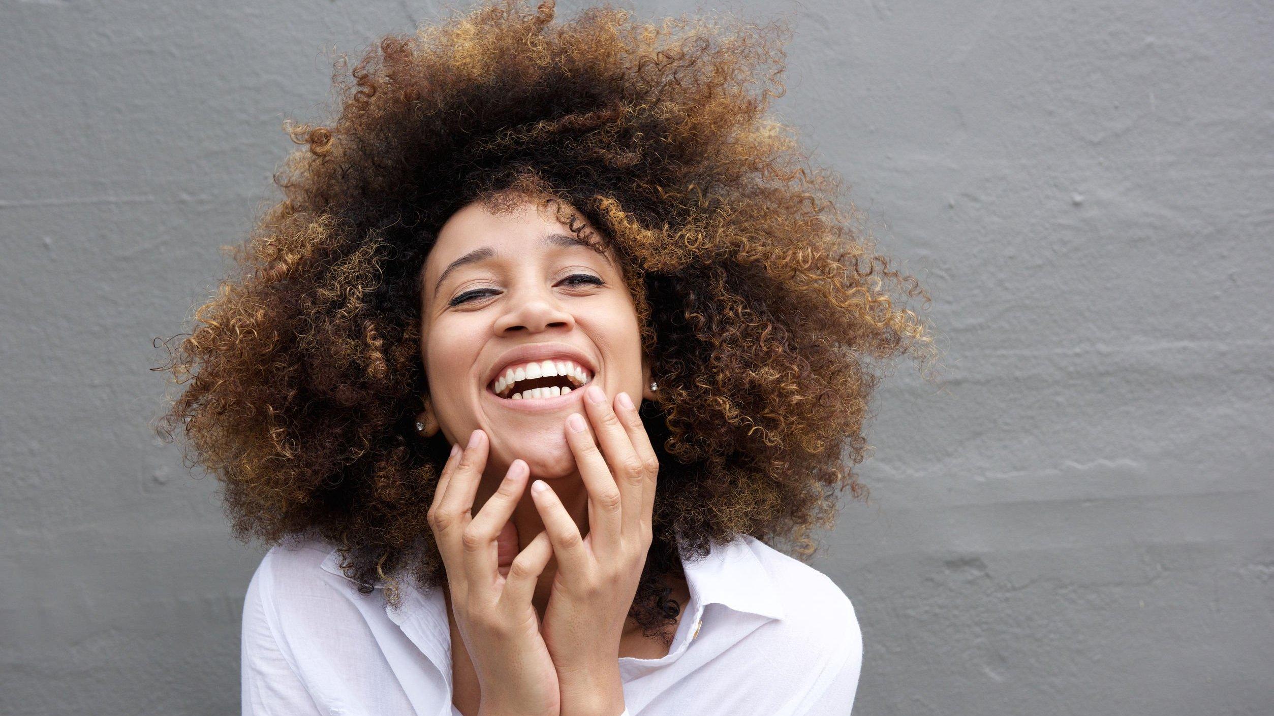 Mulher sorrindo com suas mãos perto da boca