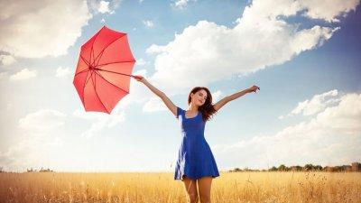 Mulher com vestido azul e braços abertos segurando guarda-chuva vermelho em campo e céu ao fundo