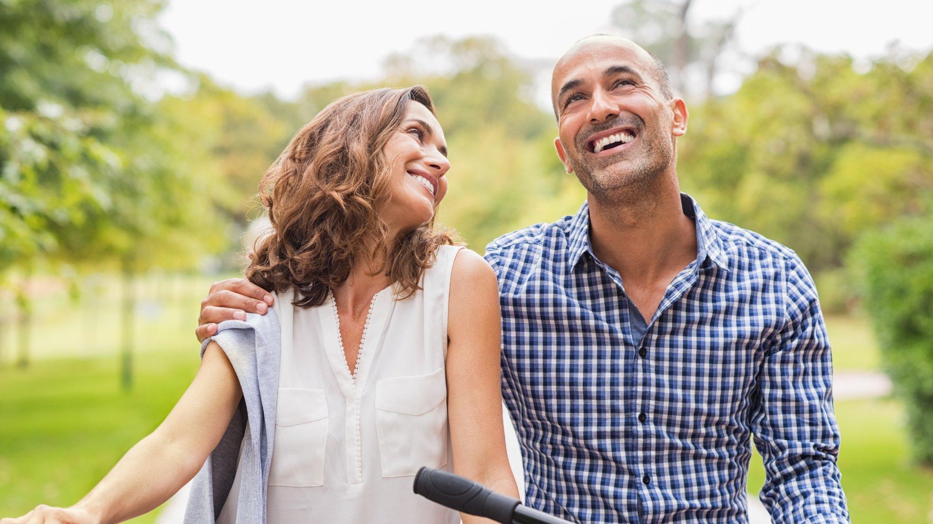 Casal feliz andando de bicicleta no parque