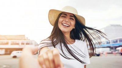 Mulher de cabelos lisos e chapéu sorrindo para a câmera