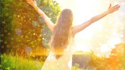 Mulher com cabelos compridos e usando um vestido, de costas para a câmera com os braços erguidos para o alto, em um campo gramado com árvores. A luz do sol atinge a mulher e a lente da câmera.
