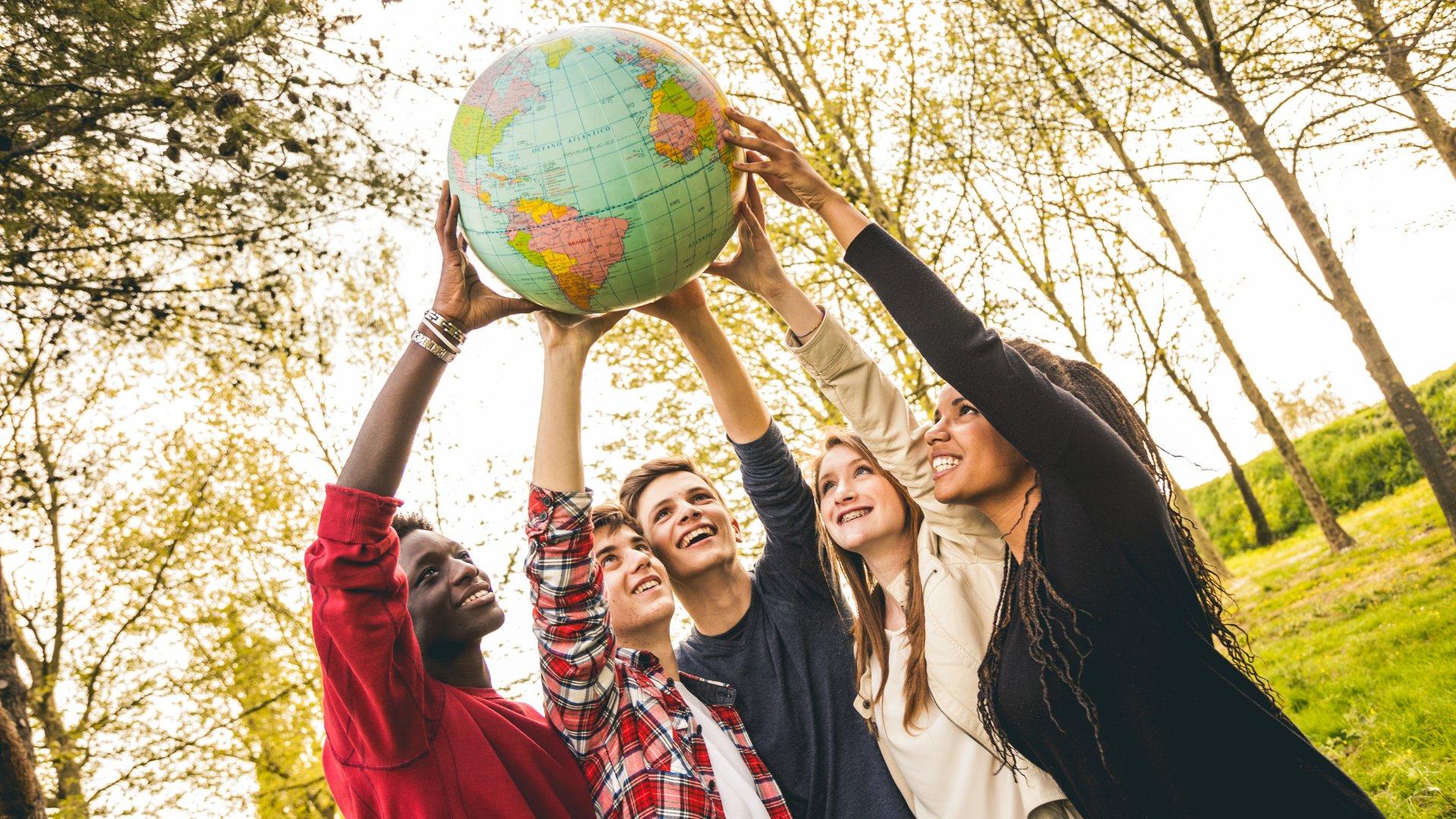 Grupo de jovens sorrindo e erguendo um globo terrestre para cima