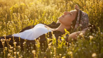 Mulher deitada em um gramado com os olhos fechados