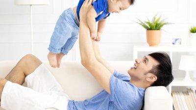 Homem deitado em sofá, segurando bebê para cima, enquanto olha para ele.