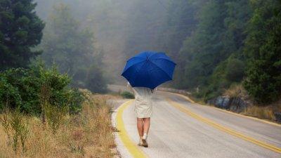 Mulher com capa de chuva e segurando um guarda-chuva, andando em uma rodovia deserta.