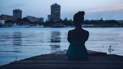 Mulher sentada em frente a um lago.