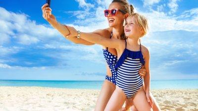 Mulher adulta com menina pequena em praia,. As duas estão ajoelhadas na areia e estão tirando uma selfie.