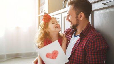 Pai e filha sentados olhando um para o outro enquanto seguram um cartão de coração